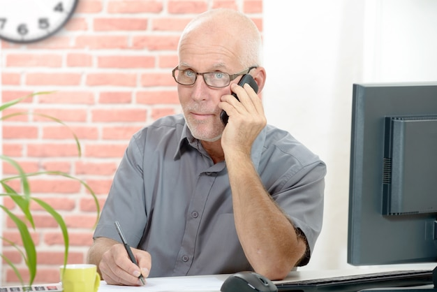 Businessman sitting at desk talking on the phone