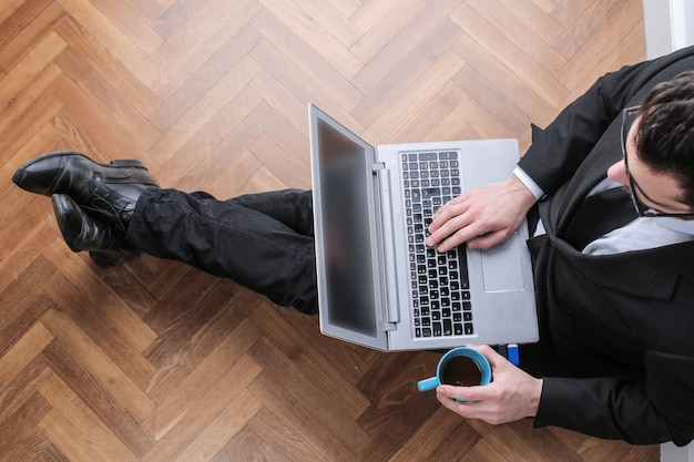 Businessman sitting on the floor with a laptop