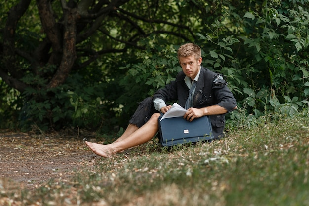 Businessman sitting on the ground on desert island