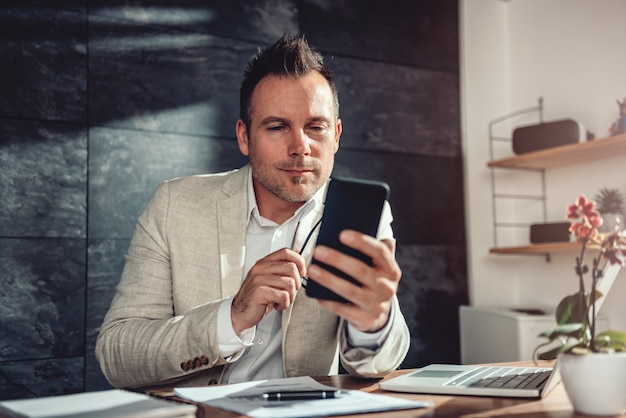 Businessman sitting at his desk and reading text messages on smart phone