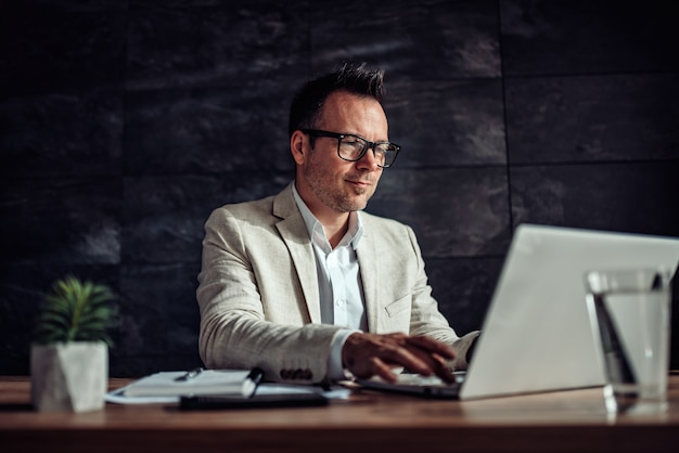 Businessman sitting at his desk and using laptop in the office
