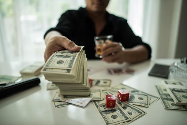 Бизнесмен сидел в бизнес-центре бар курить сигары и пить виски и деньги на столе