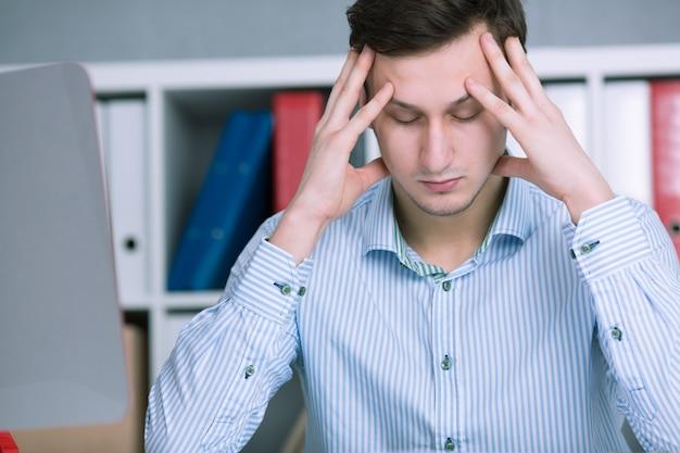 Бизнесмен, сидя в стрессовой ситуации в офисе. держите руки за голову и пытайтесь успокоиться
