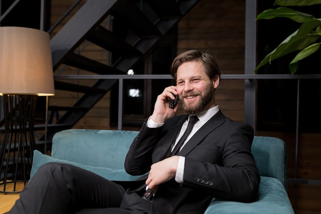 Бизнесмен сидит в стильном ресторане в расслабляющем деловом костюме и использует телефон для общения