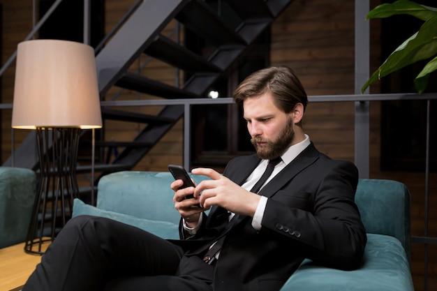 Бизнесмен сидит в стильном ресторане в расслабляющем костюме и использует телефон для общения