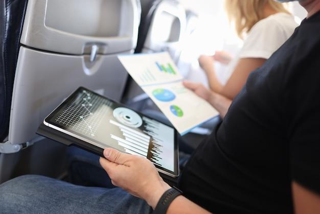 飛行機のキャビンに座っているビジネスマンは、タブレットやドキュメントでビジネスチャートを研究します