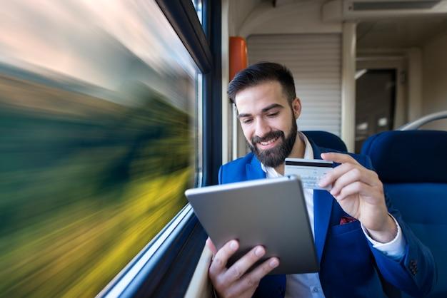 편안한 객실에 앉아 기차로 여행하는 동안 신용 카드로 온라인 지불 사업가.