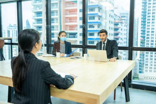 Бизнесмен, сидя на собеседовании, портрет молодой женщины, имеющей собеседование с менеджером и секретарем в финансовой компании.