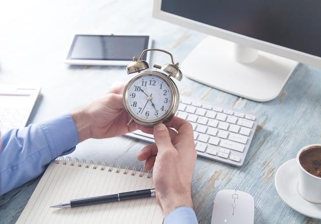 Бизнесмен сидит в офисе и держит будильник.