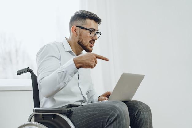 Бизнесмен, сидя в инвалидной коляске и используя ноутбук дома