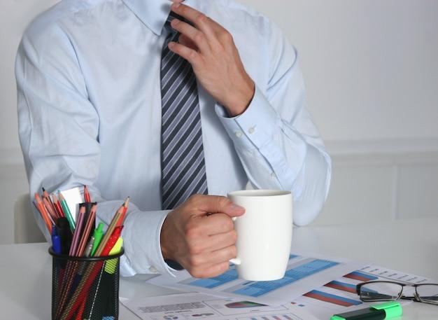 Businessman sitting at office desk having a coffee break