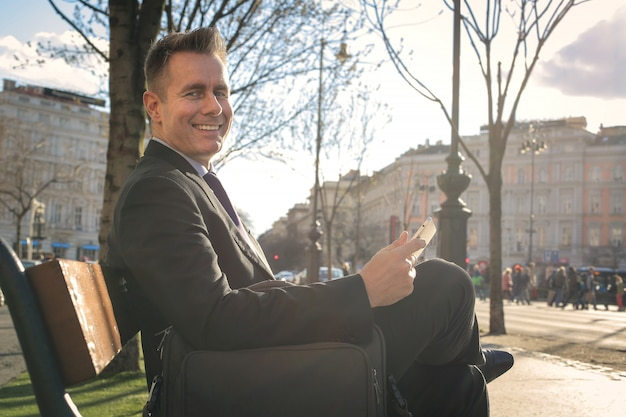 Бизнесмен сидит на скамейке Premium Фотографии