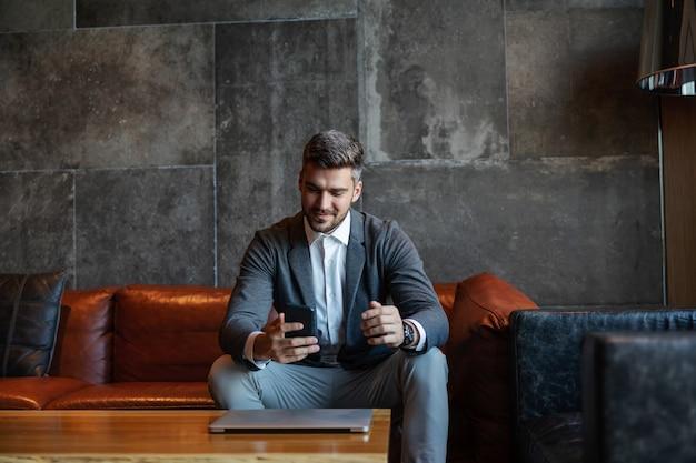 ユニークでモダンな空間のソファに座って、電話とラップトップを使用しているビジネスマン。