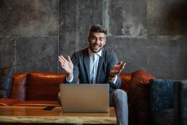 사업가 비즈니스 홀에서 소파에 앉아 동료와 온라인 확대 / 축소 화상 통화를합니다. 전화 회의, 통신, 온라인 회의