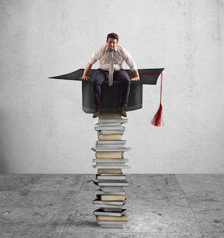 졸업 모자와 책 더미에 앉아 사업
