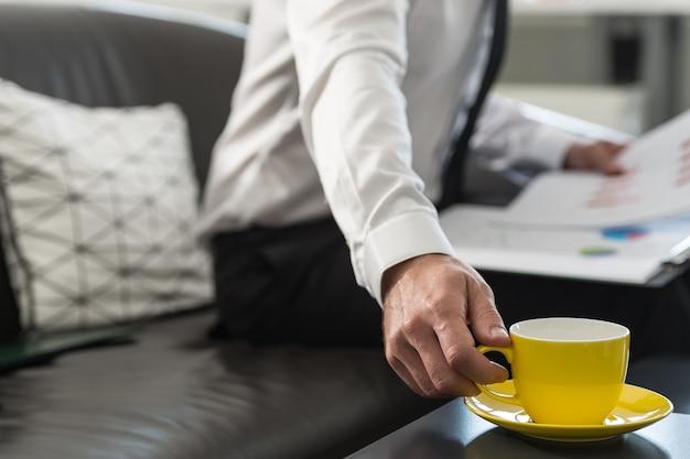사업가 서류와 함께 사무실 소파에 앉아 커피 한 잔에 도달 그의 무릎에 보고서.