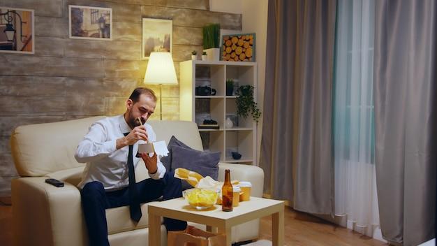 Бизнесмен, сидя на диване, ест лапшу на вынос из коробки после работы в своей квартире, смотря телевизор.