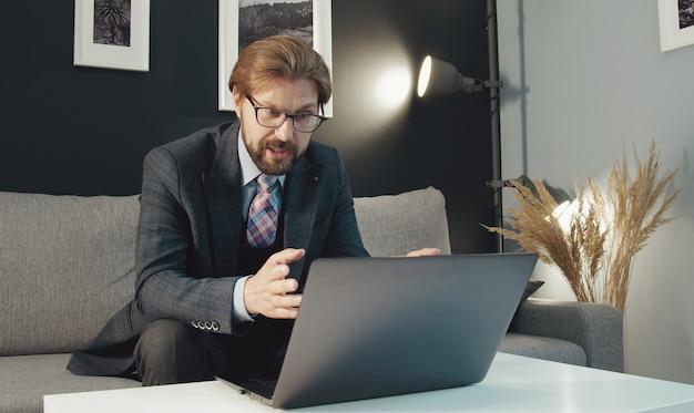 Бизнесмен, сидя на диване перед ноутбуком, жестикулируя, разговаривая с кем-то через интернет