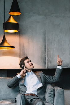 Businessman sitting on sofa talking through cellphone looking up