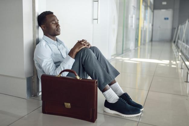 Бизнесмен, сидя на полу в коридоре офиса