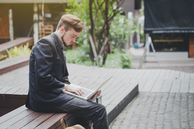 Businessman sitting outdoors unhappy at work.