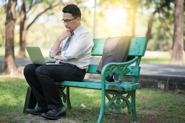 Businessman sitting on the park bench with laptop on his lap and checking the email.