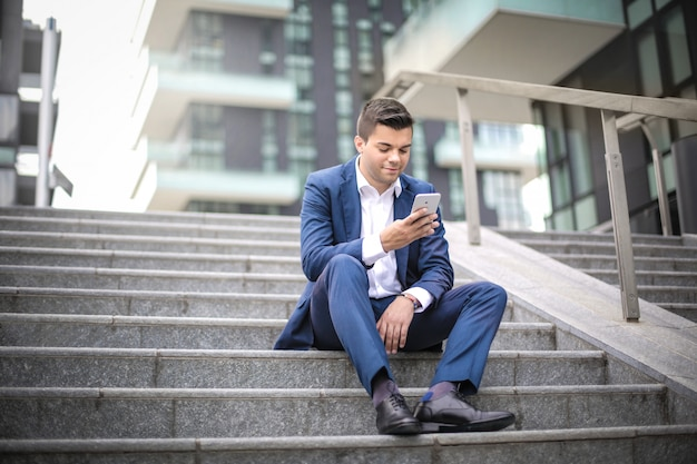 Businessman sitting on stairs in the street, checking his smart phone