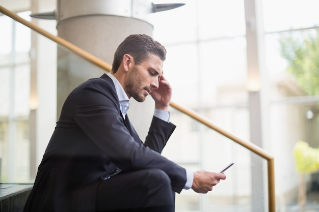 Businessman sitting on steps and using mobile phone