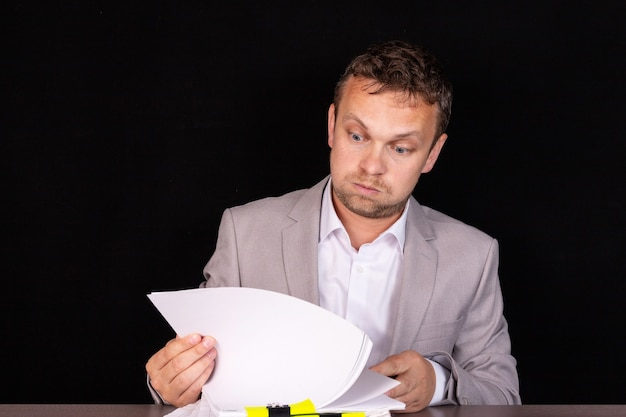 Businessman sitting at the table with documents.