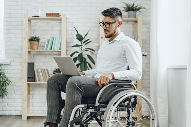 Businessman sitting in wheelchair and using laptop at home