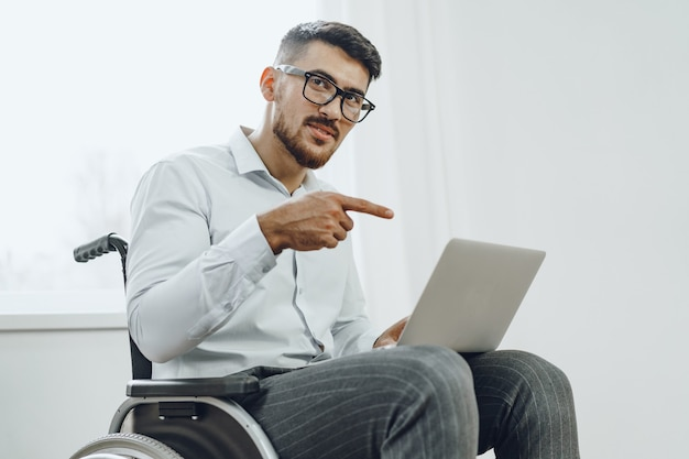 Businessman sitting in wheelchair and using laptop