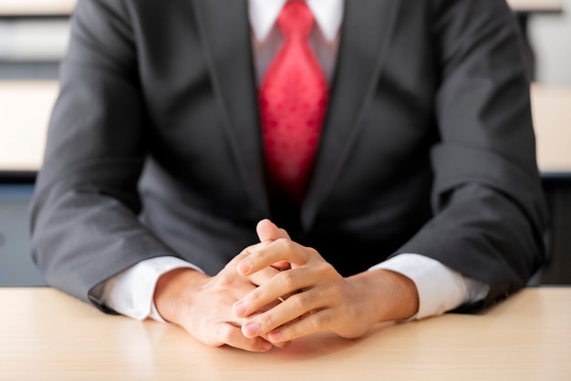 Businessman sitting with hands on the desk