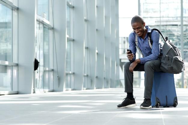 駅、荷物、携帯電話に座っているビジネスマン