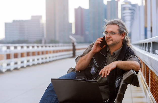Businessman sitting on the with new york cityscape with smart phone in outdoor.