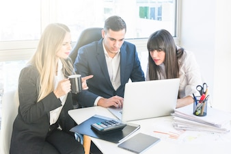 Businessman sitting with two women working in the office