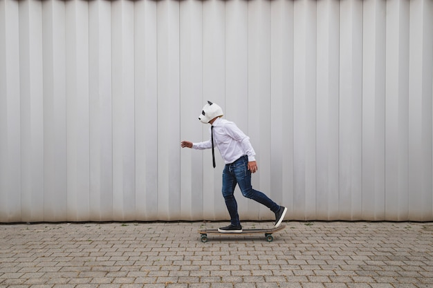 Businessman skateboarding on longboard with a panda bear mask against gray wall