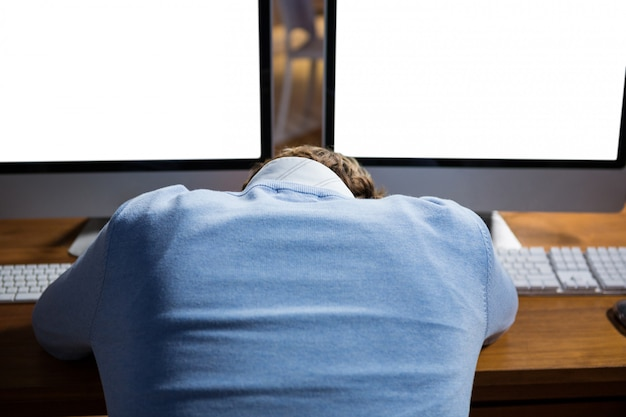 Businessman sleeping on desk while working in office
