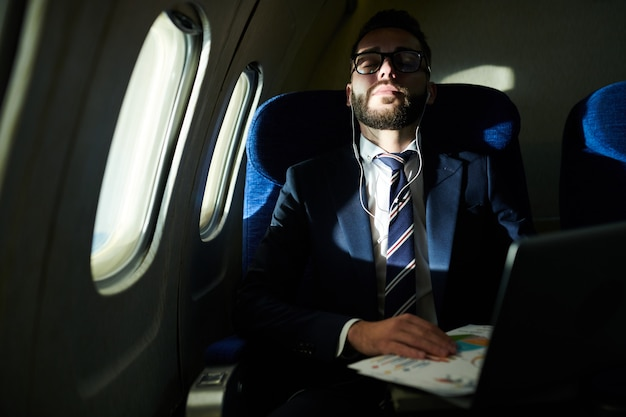 Businessman sleeping in flight
