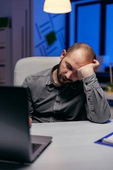 과로 때문에 회사 사무실에서 자고 있는 사업가. 워커홀릭 직원은 중요한 회사 프로젝트를 위해 사무실에서 밤늦게 혼자 일하기 때문에 잠이 듭니다.