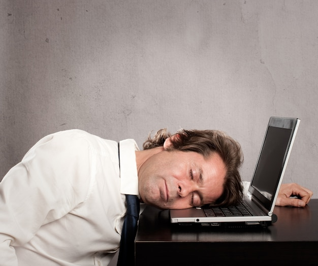 Businessman sleeping on laptop on gray background