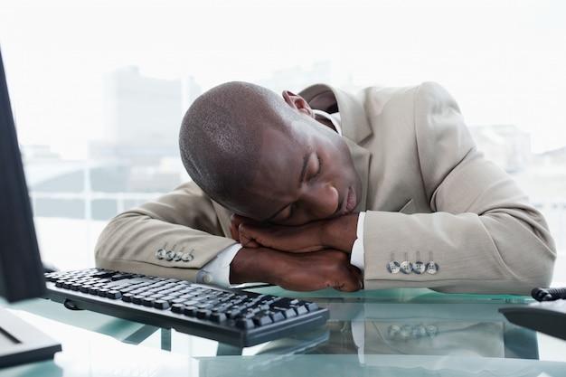 ビジネスマン、机の上で寝る