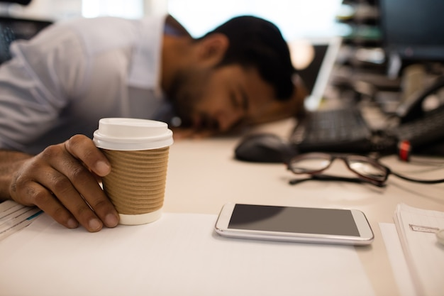 Businessman sleeping while holding disposable coffee up on desk