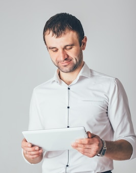 A businessman smiles and holds a white tablet in his hands. a man is standing in luxurious shirt