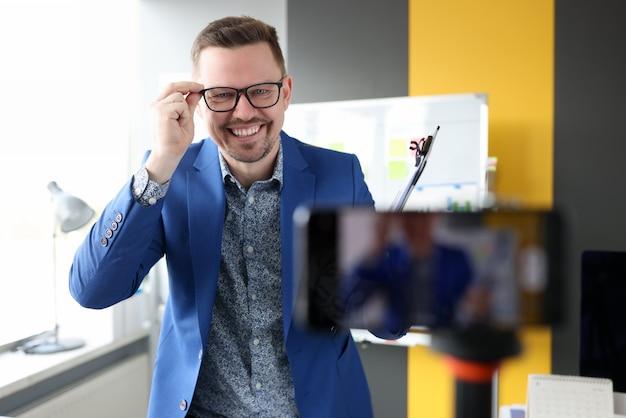 사업가 웃 고 휴대 전화 카메라 온라인 비즈니스 앞에서 안경 조정