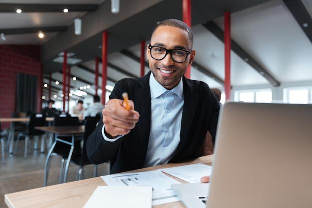Бизнесмен улыбается и указывая с помощью pncil на рабочем месте