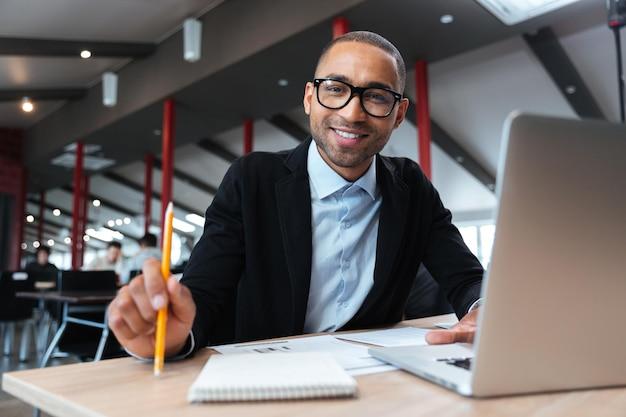 Бизнесмен, улыбаясь на рабочем месте и держа карандаш