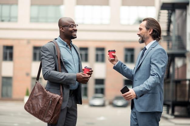 Бизнесмен улыбается. бородатый бизнесмен улыбается, разговаривая с коллегой и пьет кофе