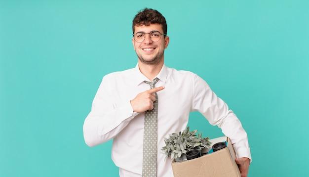 사업가는 즐겁게 웃고 행복감을 느끼며 옆과 위쪽을 가리키며 복사 공간에 물건을 보여줍니다. 해고 개념