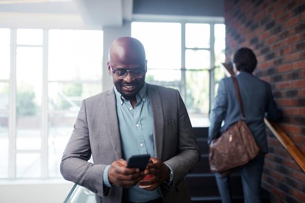 ビジネスマンの笑顔。メッセージを読みながら笑顔の眼鏡をかけている浅黒い肌のひげを生やしたビジネスマン