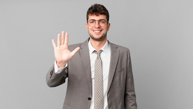 Businessman smiling and looking friendly, showing number five or fifth with hand forward, counting down